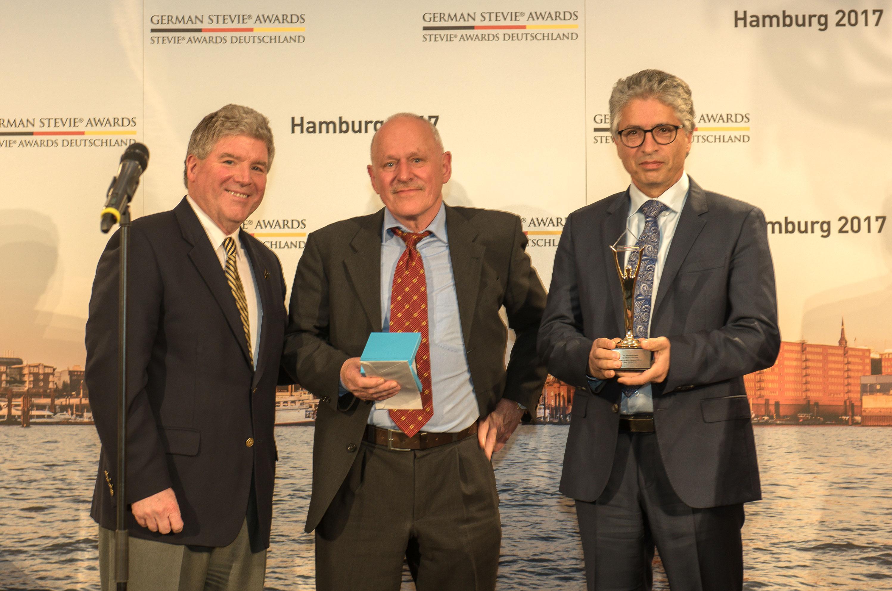 Saeid Fasihi mit Pressesprecher Martin Müller und Stevie Awards Präsident Michael Gallagher bei der Preisverleihung der GSA17